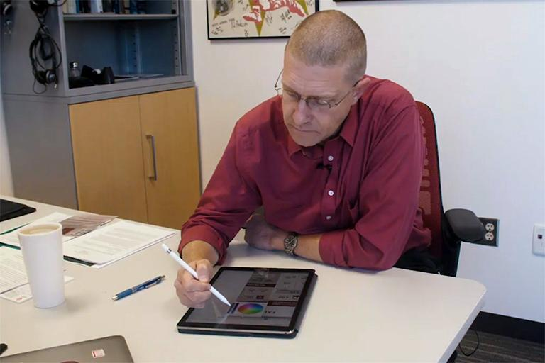 Chris Foley sitting at a desk while grading student work using an Apple Pencil and an iPad.