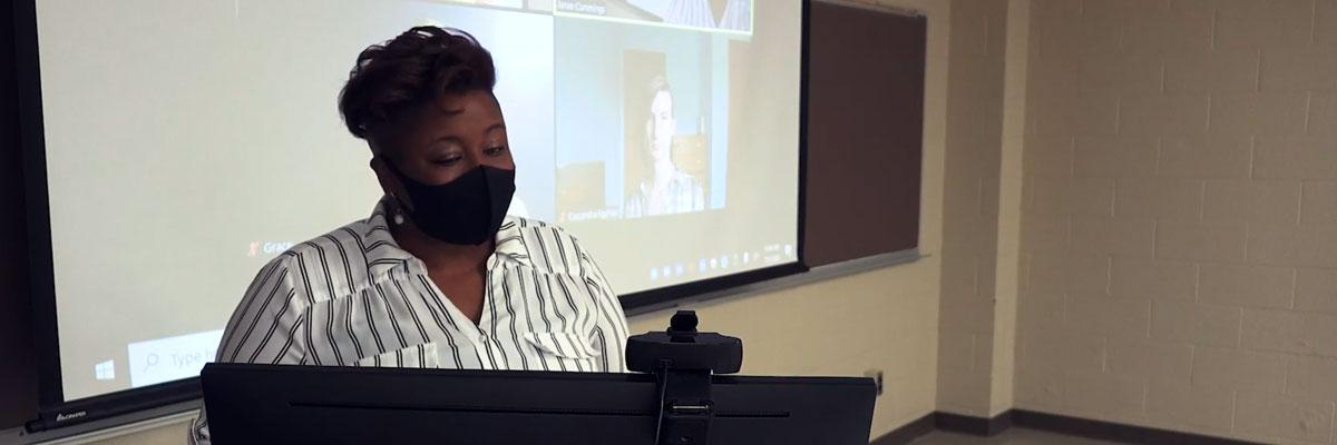 Photo of an instructor at the teaching computer with students participating via Zoom behind her