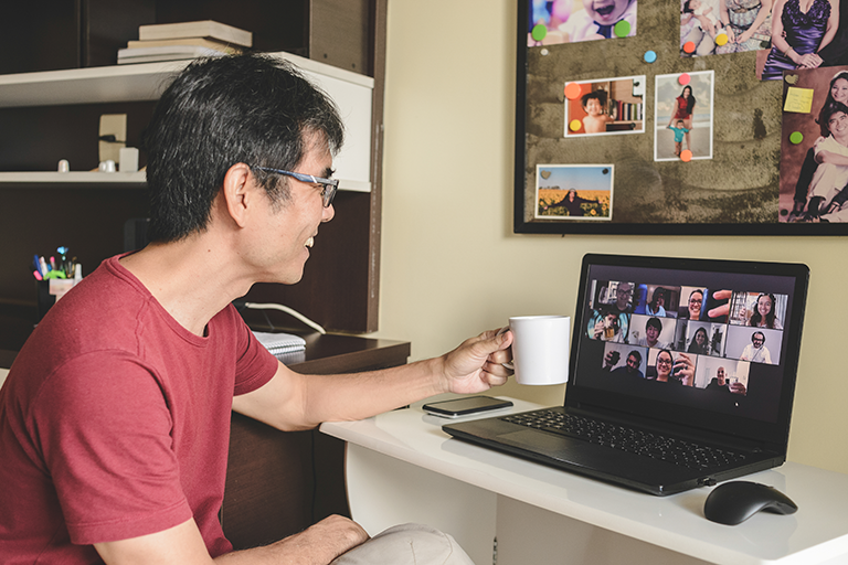 Photo of man drinking coffee during a Zoom meeting