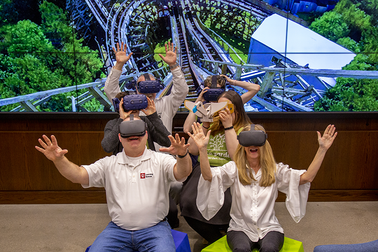 Photo of Learning Spaces team experiencing a virtual reality roller coaster