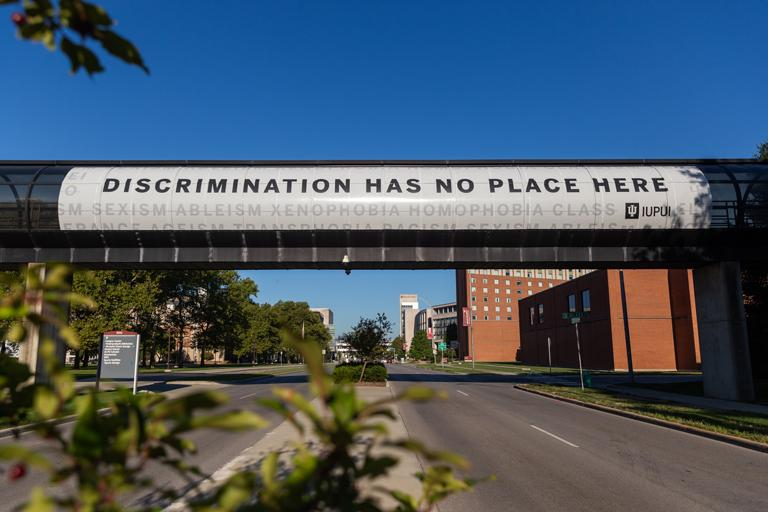 Road overpass on the IUPUI campus painted with the words, Discrimination has no place here.