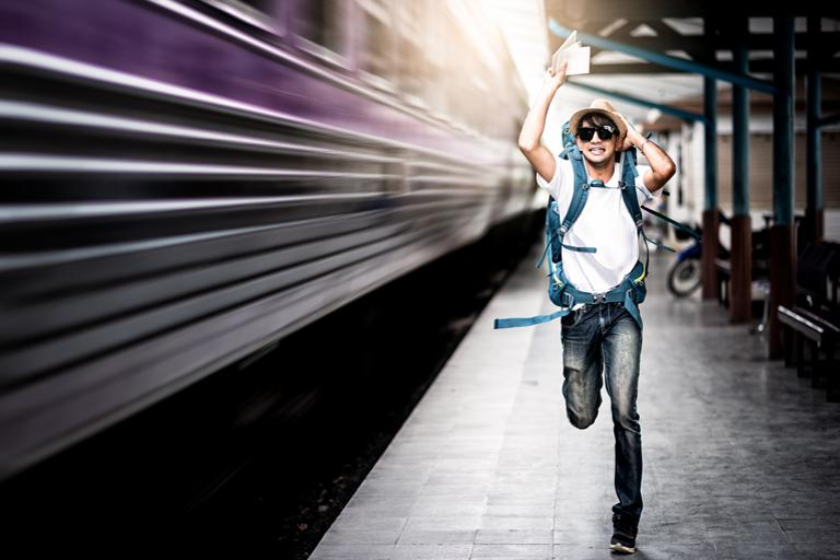 A man wearing a backpack and holding tickets in his hand is on a train platform running after a moving train